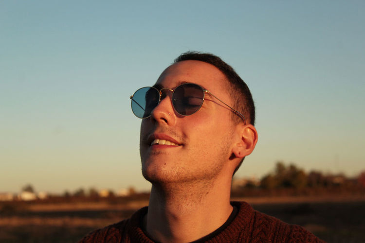 Portrait of young man wearing sunglasses against sky during sunset