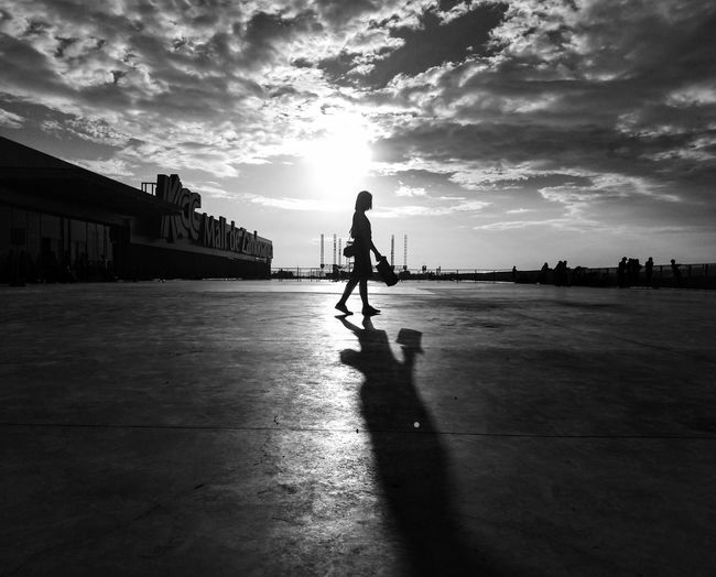 Silhouette woman walking in city against sky during sunset