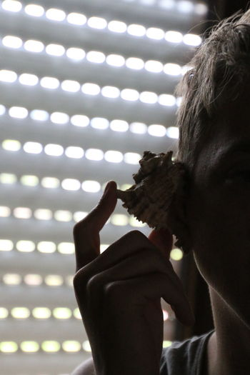 Cropped Image Of Person Listening To Sea Shell Against Window