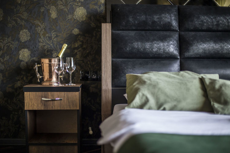 Wineglasses with bucket on side table in bedroom