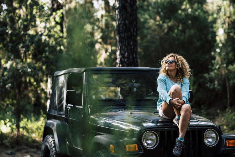 Woman wearing sunglasses while sitting on car