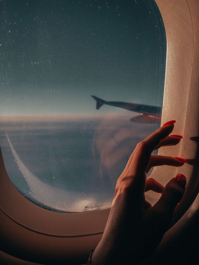 Aerial view of hand against sky seen through airplane window