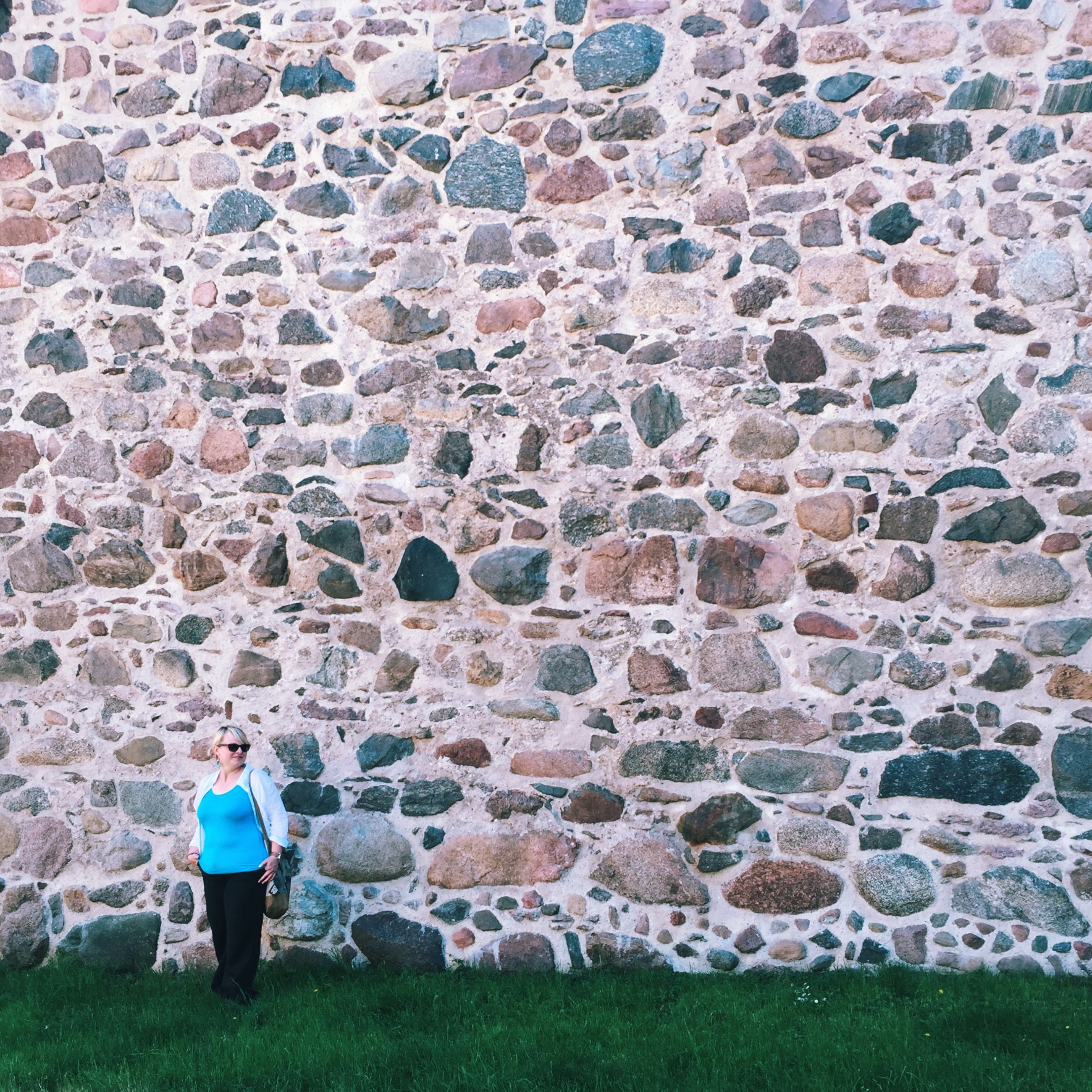 lifestyles, leisure activity, casual clothing, full length, standing, person, grass, men, rear view, wall - building feature, built structure, architecture, walking, building exterior, day, outdoors, stone wall, brick wall