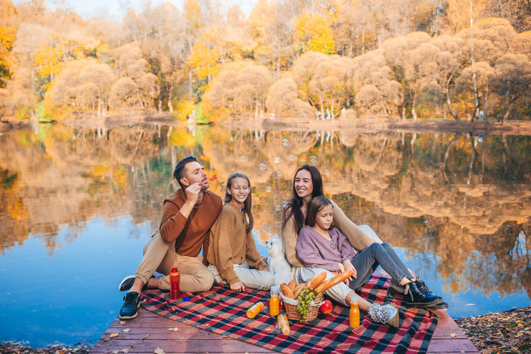 Group of people sitting by lake during autumn
