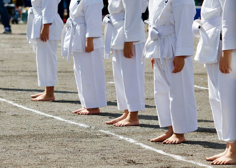 Low section of children standing during martial arts event