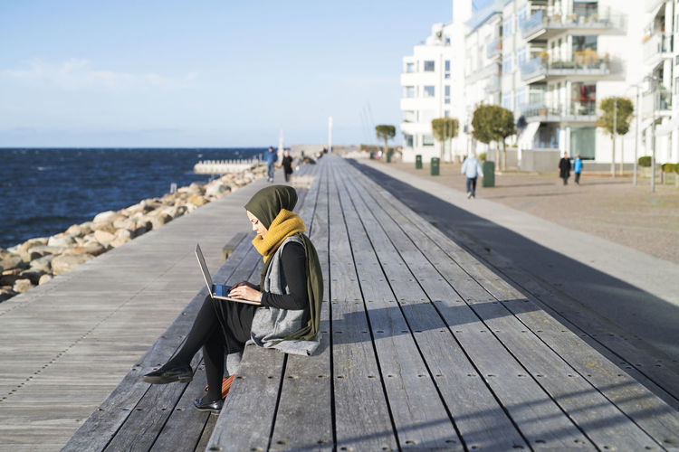 Woman sitting on footpath by sea against sky in city