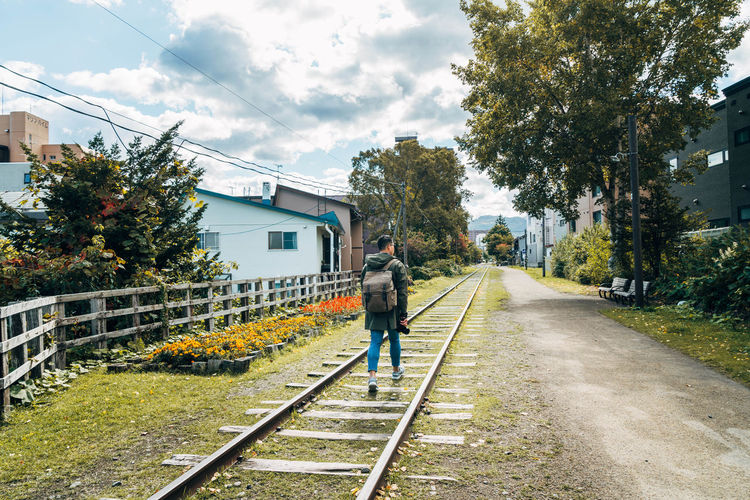 Rear view of man walking on railroad track