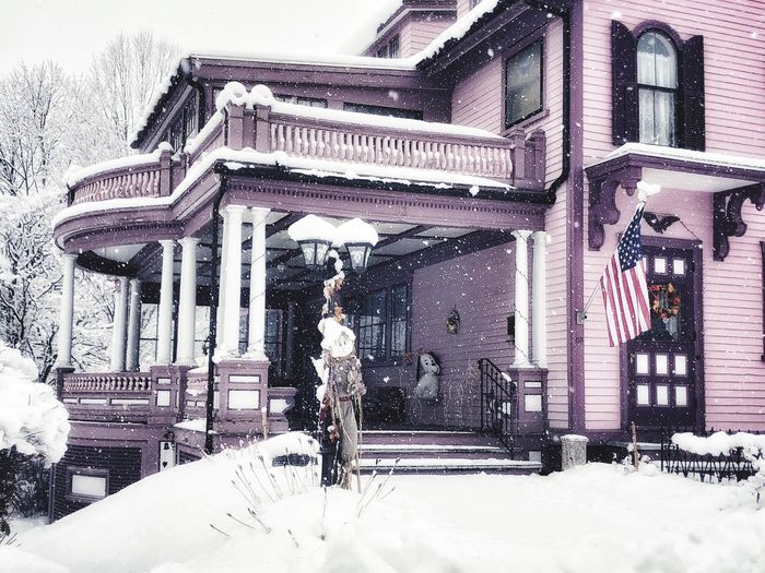 Old Victorian Style Home in New England . Large porch with American flag in the doorway. American Flag Snow Falling Down Pink House Snow Covered Large Snowdrops New Hampshire, USA Snow Falling Down Old Victorian Home Cloudy Sky Snow Flakes ❄⛄ New England Charm Outdoor Photography Large New England Home Old Victorian Home Snow Architecture Building Exterior Winter Built Structure Cold Temperature Building Snowing Nature