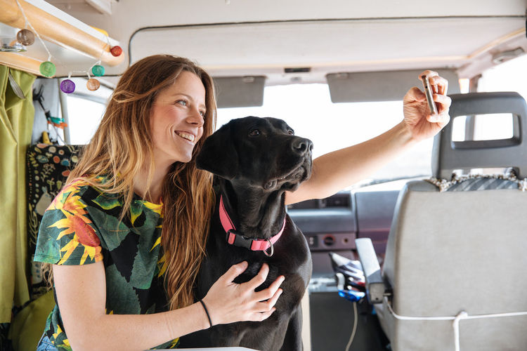 Woman Taking Selfie With Dog In Camper Van