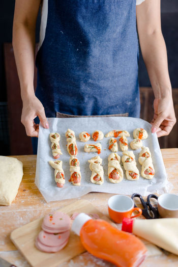Midsection of woman holding food in baking sheet
