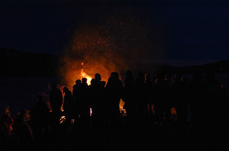 Silhouette people by bonfire against sky at night