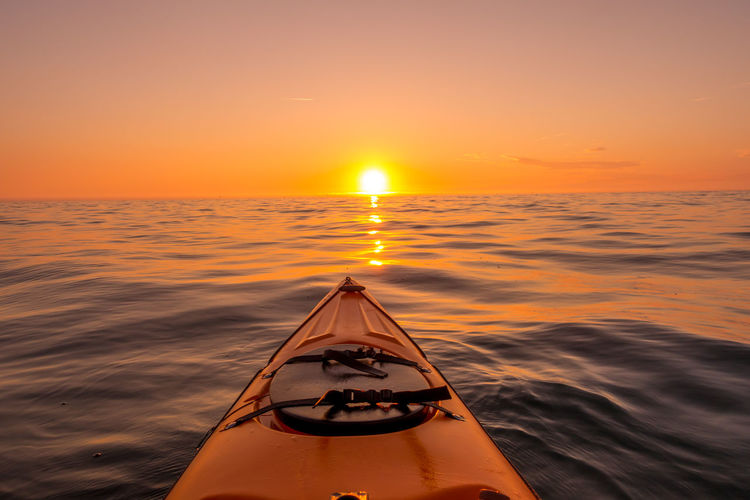 Cropped image of kayak in sea against sky during sunset