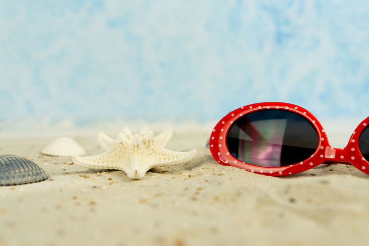 A red sunglasses with white dots in the sand, with shells and starfish Sunglasses Sand Maritime Beach Holiday Shells Starfish  Red Dotted White Background Sea Shell Travel Summer Sun Vacation Tropical Concept Sunny Coast Seashore Nature Seashell Relaxation Shore Colorful Nobody Tourism Leisure Recreation  Glasses Seaside Sea Life Water Selective Focus Personal Accessory No People Outdoors Marine
