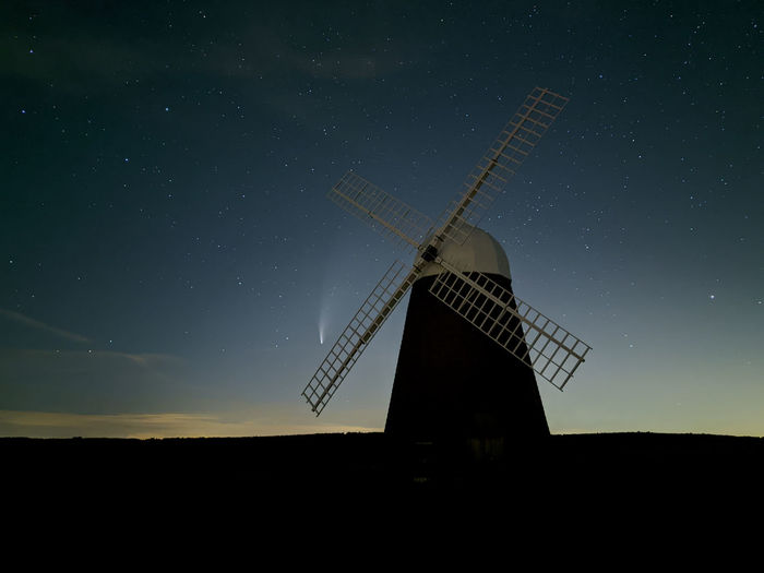 Traditional windmill on field against sky at night with comet neowise