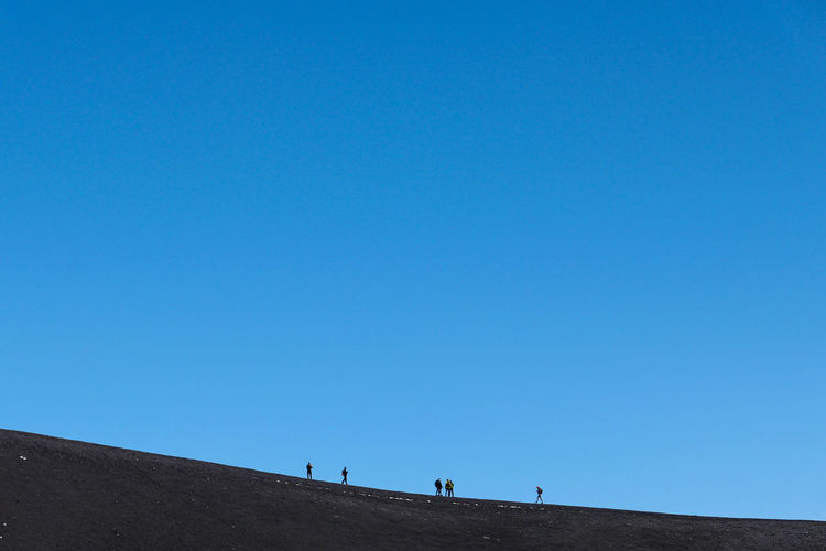 People walking on land against clear blue sky