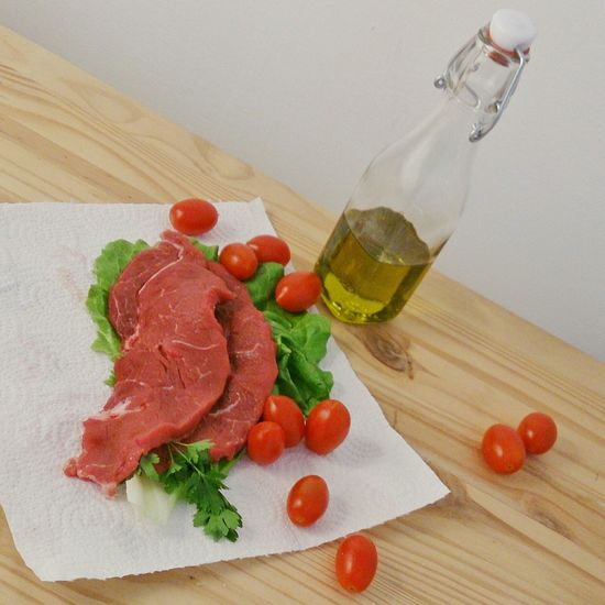 High angle view of raw meat and tomatoes on wooden table