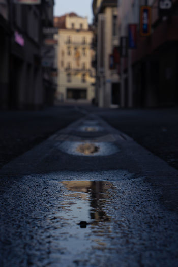 Surface level of wet road by buildings in city