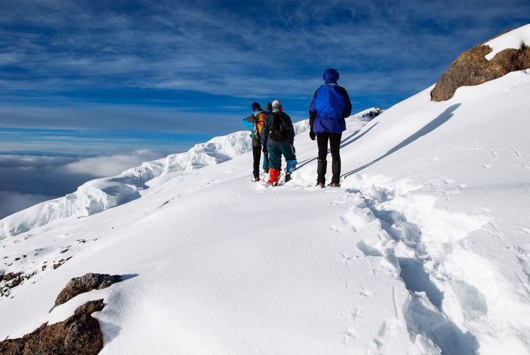 Rear view of people climbing snow covered mountain