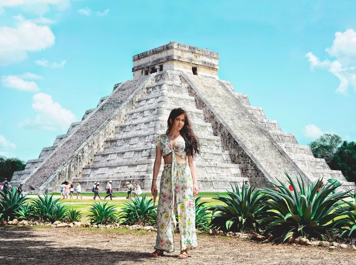 Full Length Of Woman Standing By Ancient Building Against Sky
