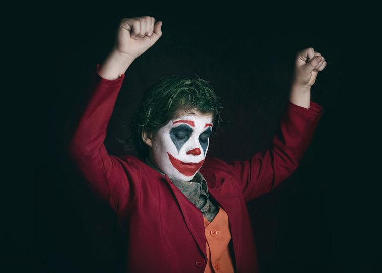 Boy with face paint against black background