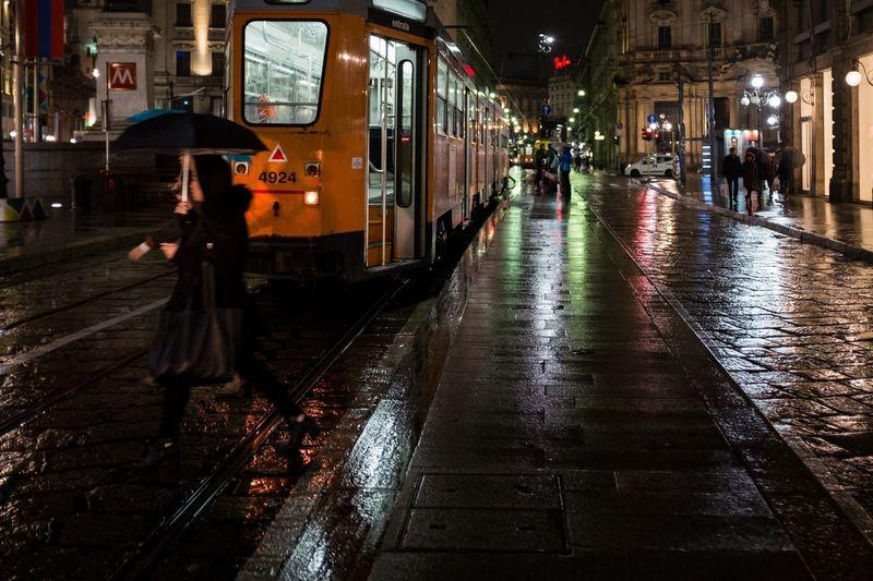 People walking on wet illuminated city at night