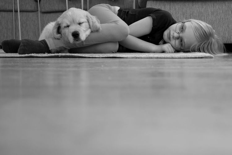 Girl and dog resting on floor at home