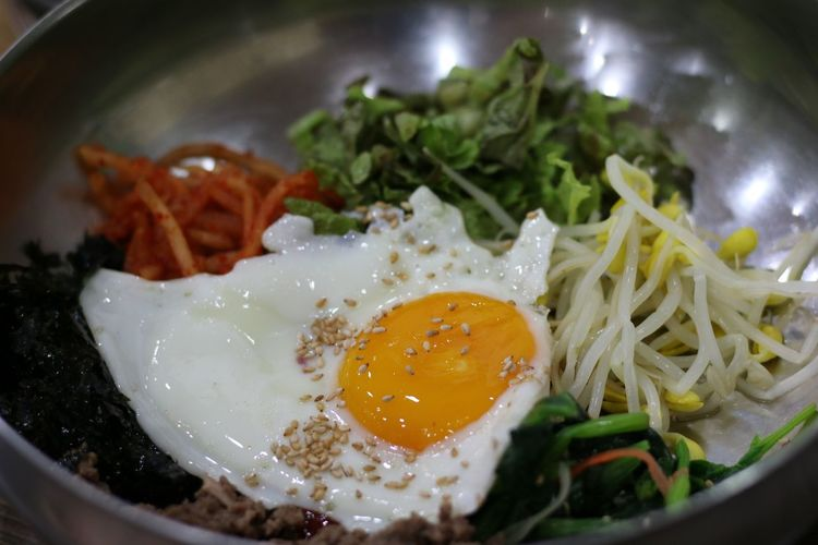 Close-up of fried egg and bean sprouts with salad in bowl