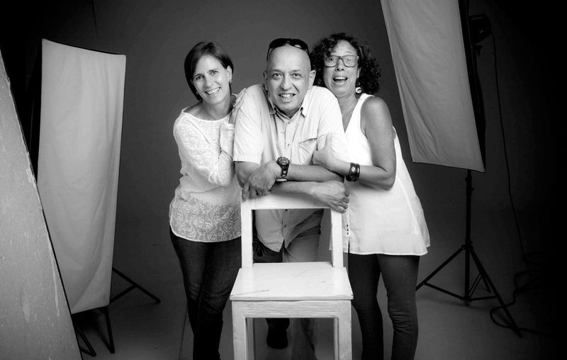 Portrait Of Smiling Family In Studio Shot Standing By Reflectors