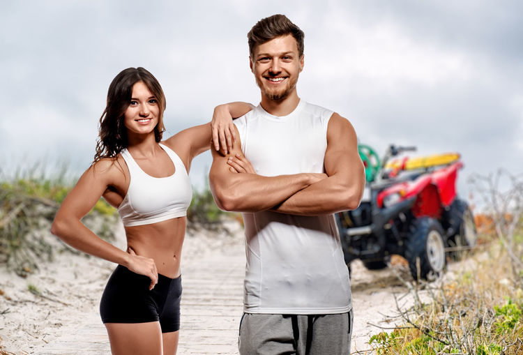 Young and beautiful athletic woman and man posing outdoors Athlete Athletic Bodybuilding Couple Man Woman Attractive Beach Beauty Brunette Fitness Fitness Model Handsome Muscular Build Outdoors People Physique  Smiling Sport Sportive Sports Clothing Strong Summer Woman And Man Young Adult