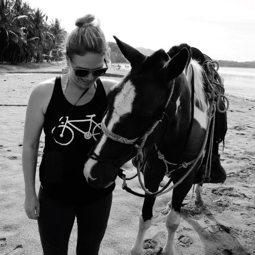Woman Standing With Horse On Sand At Beach Against Sky