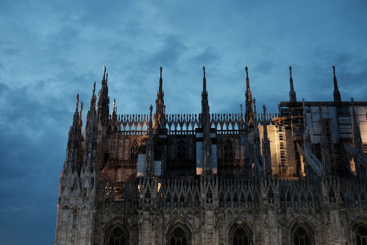 Low angle view of milan cathedral against cloudy sky at dusk