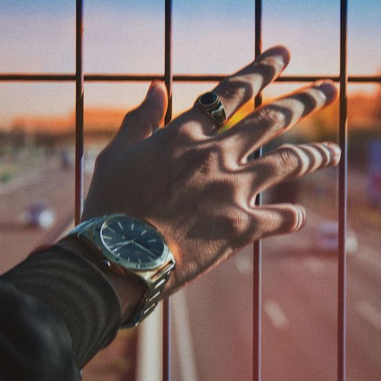 Cropped hand of man with wristwatch touching metal grate against highway