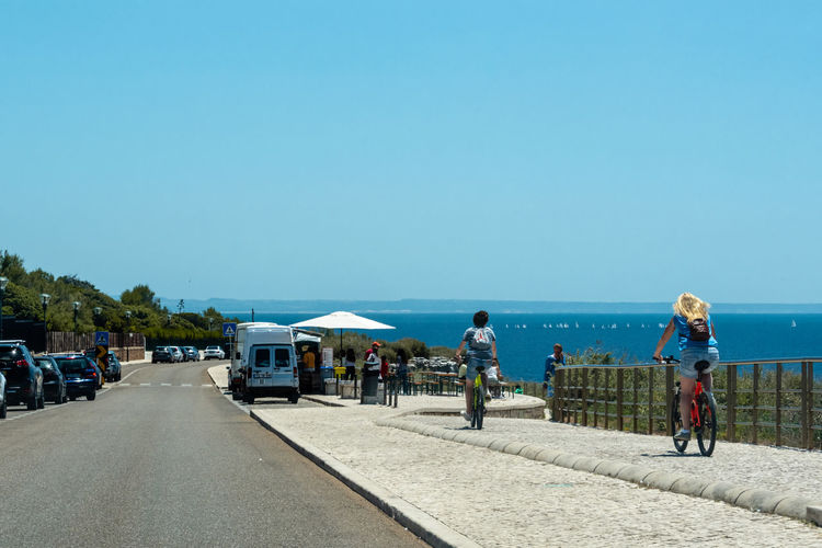 People on road by sea against clear blue sky