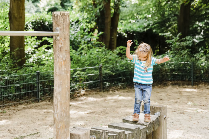 Full length of girl standing on wood at playground