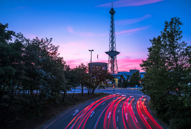 Light trails on road with berlin radio tower (funkturm) against sky