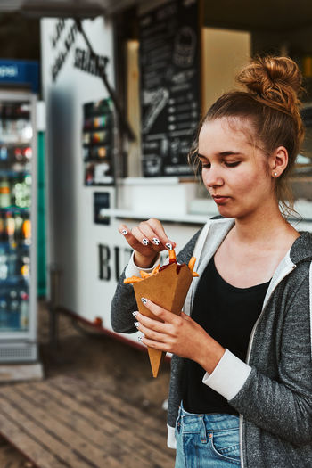 Teenage girl eating potato fries from carton cone standing in front of food truck