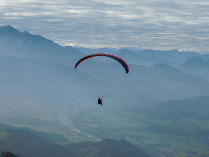 Person paragliding over mountains against cloudy sky
