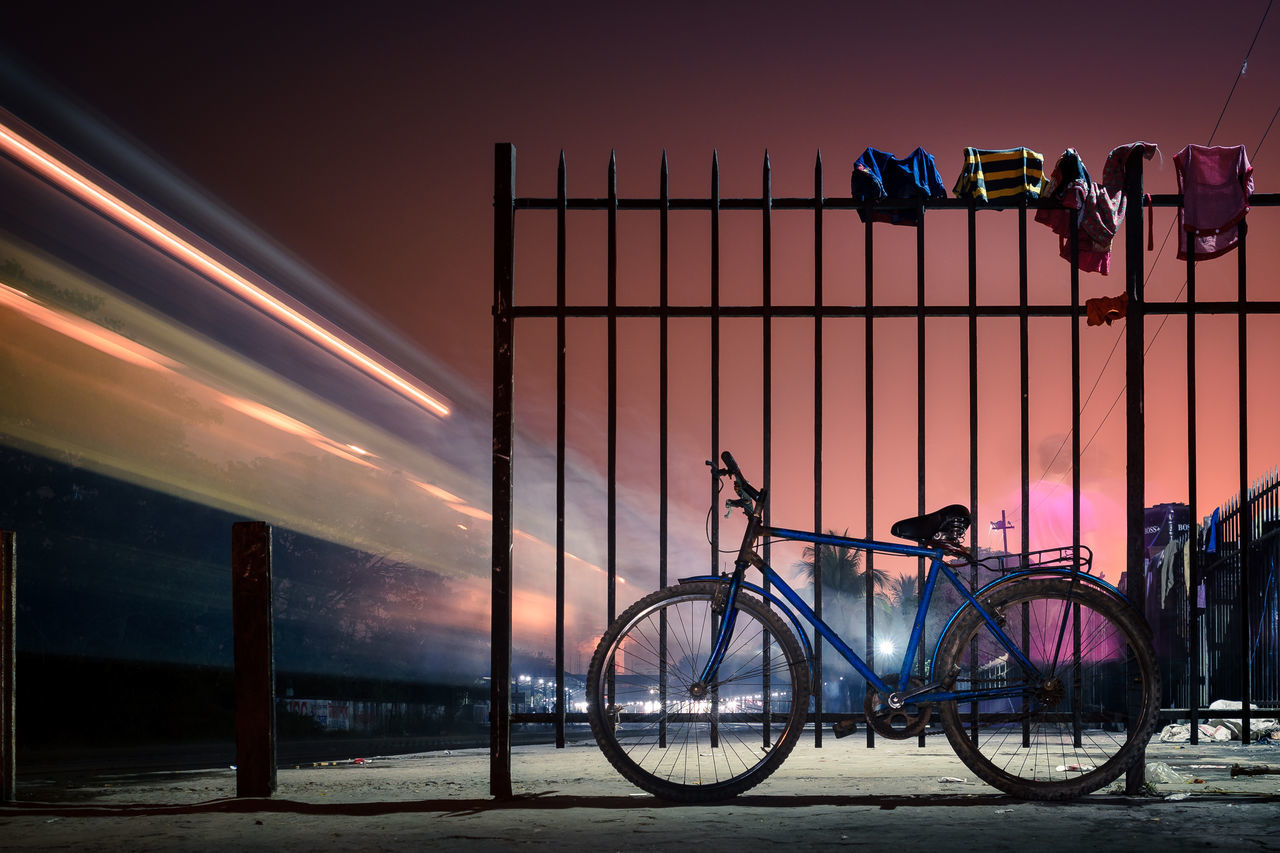 Blurred train with parked bicycle against the gate