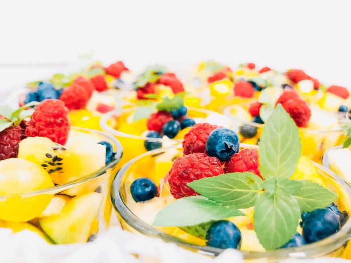 Close-up of fruits in bowls against white background