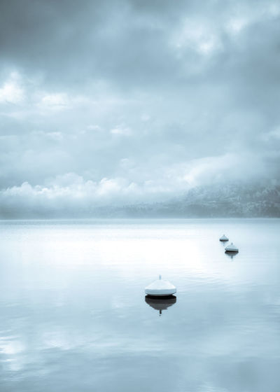 Monochrome landscape of buoys floating in calm lake with water reflecting winter storm clouds and fog with mountain in distance Blue Tones British Columbia, Canada Lonely Storm Light Buoys Calm Water Cold Fog Gloomy Mist Monochrome Moody Mountain Nature Outdoors Peaceful Reflection Serene Skaha Lake Sky South Okanagan Storm Clouds Tranquility Water Waterfront