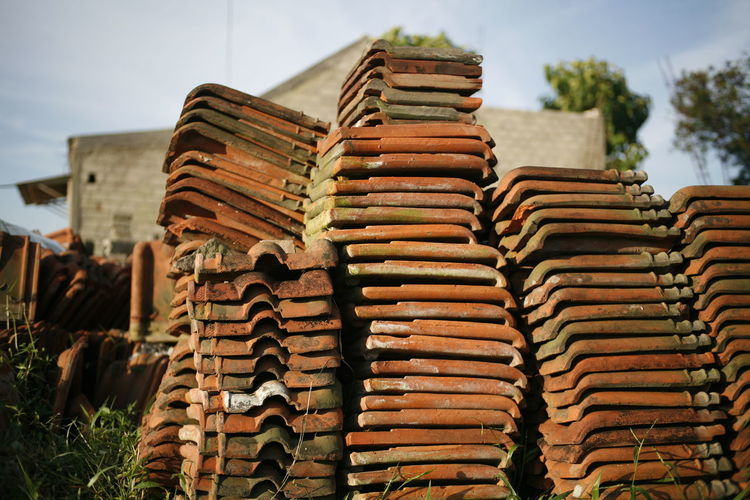 Stack of roof tiles against building