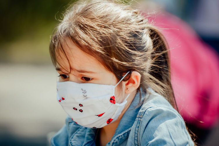 Close-up of cute girl looking down while wearing mask