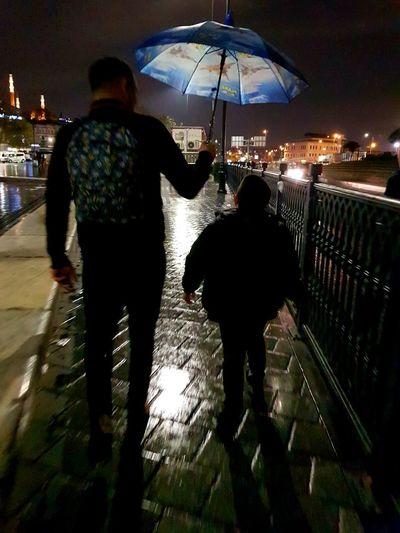 Rear view of people walking on wet street during rainy season