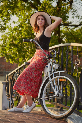 Portrait of woman with bicycle on railing