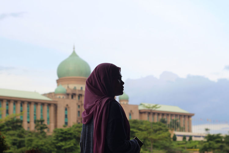 Side view of woman wearing hijab standing against mosque
