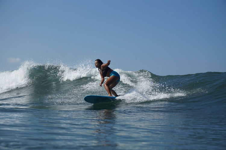Woman surfing in sea against clear sky