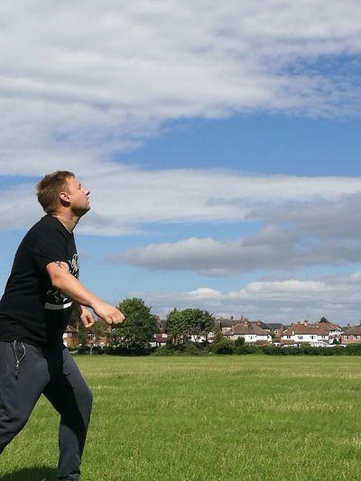 Playful man on grassy field against sky