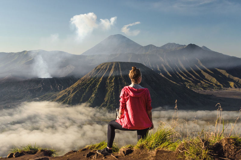 Woman sitting on land against mountain range