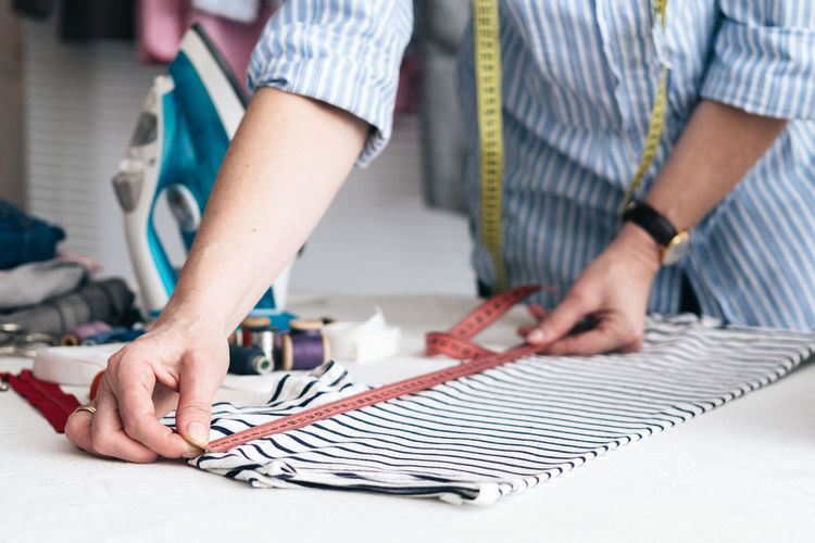 Midsection of craftswoman measuring clothing on table