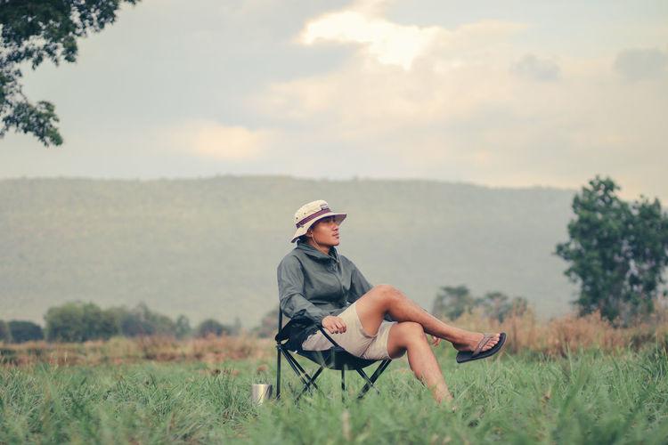 Full length of man sitting on field against sky